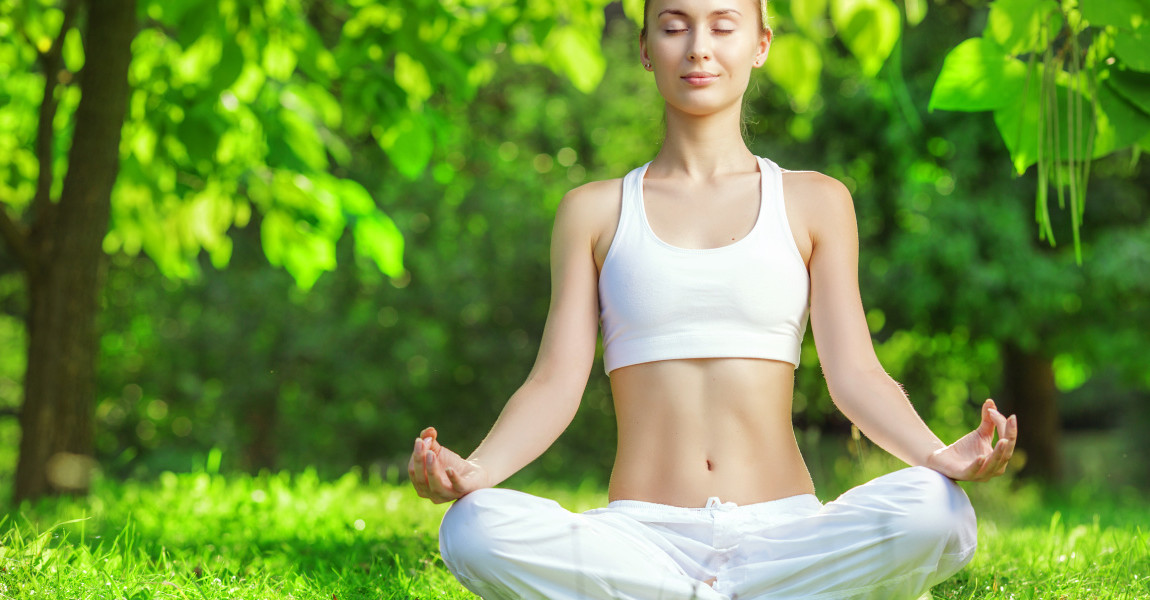 Yoga outdoors. Woman meditating in lotus position.
